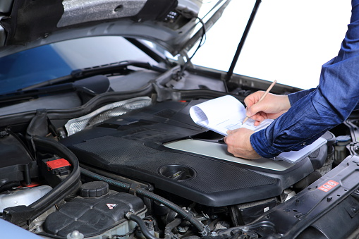 mechanic checking a car with checklist